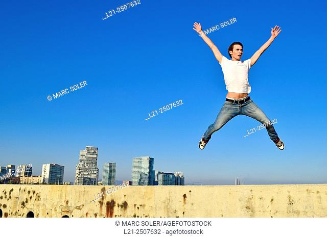 Young man jumping against city skyline. Barcelona, Catalonia, Spain