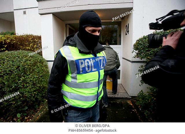 Police officers remove materials siezed during a raid carried out in a residential building in Bonn, Germany, 15 November 2016