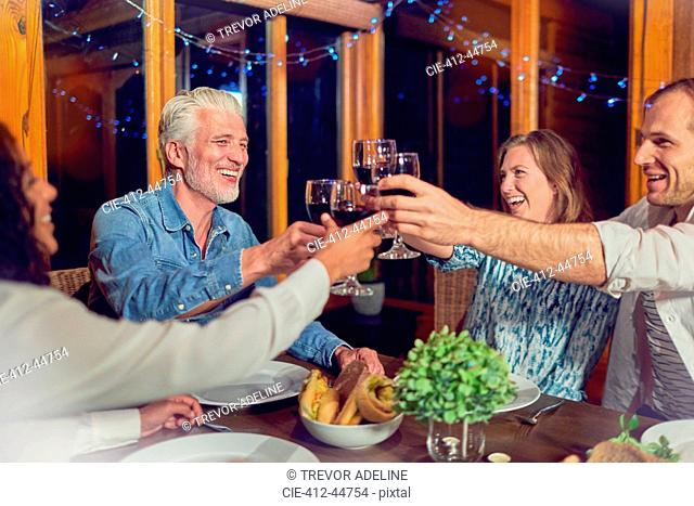 Friends celebrating, drinking red wine and enjoying dinner in cabin