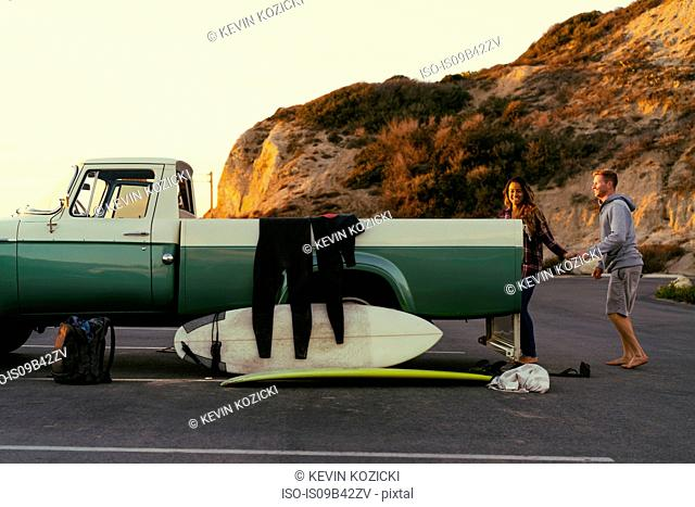 Surfing couple with pickup truck at Newport Beach, California, USA