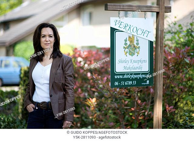 Tilburg, Netherlands. Portrait of a female real estate agent, in front of a residential house just being sold