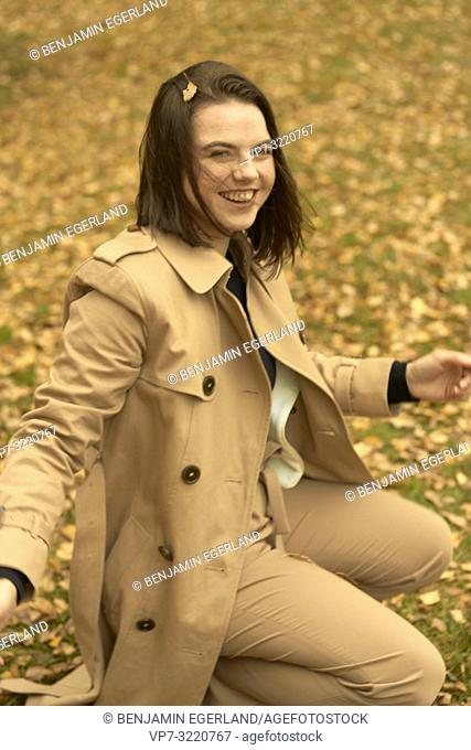 happy young woman crouching outdoors on autumn leaves, wearing coat, candid emotion, in Munich, Bavaria, Germany