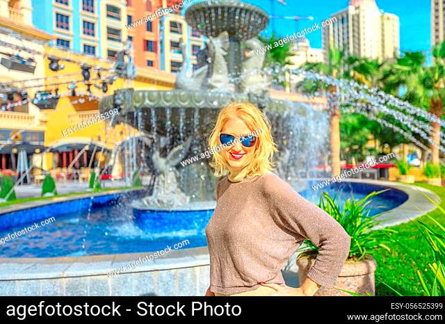 Happy blonde woman enjoys water fountain in Central Medina, an exclusive residential area in The Pearl Qatar, icon of Doha, Persian Gulf, Middle East