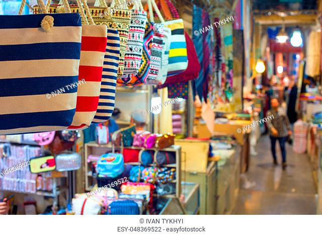 Grand Bazaar market in Tehran, rows of colorful textile crafts shops, bags in foreground, Iran