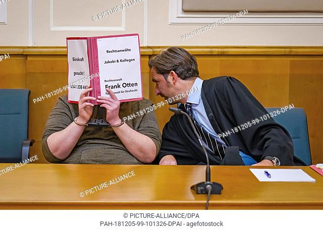 03 December 2018, Lower Saxony, Osnabrück: The lawyer Frank Otten (r) bends over to a defendant in a murder trial who is holding a file cover in front of his...