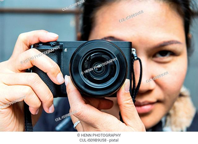 Woman taking pictures with mirrorless digital camera
