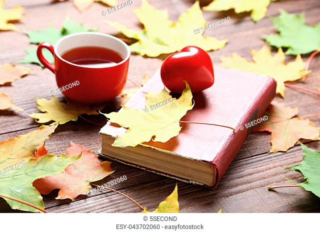 Autumn leafs with cup of tea on brown wooden table