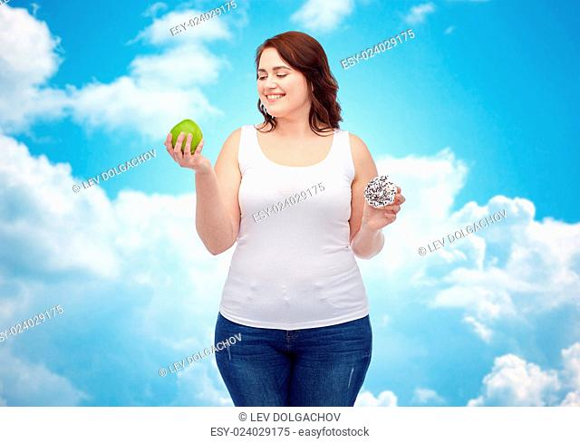 healthy eating, junk food, diet and choice people concept - smiling plus size woman choosing between apple and donut over blue sky and clouds background