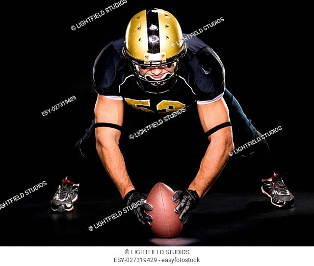 American football player in protective sportswear holding ball on dark