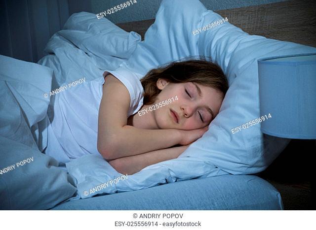 Cute Girl Sleeping On Bed In Dark Bedroom