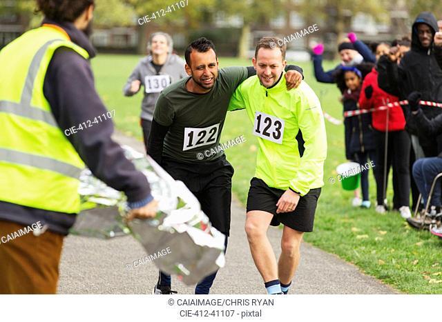 Runner helping injured man running at marathon