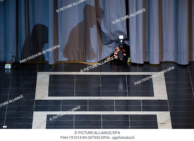 14 October 2019, Lower Saxony, Hanover: A photographer photographs through a curtain at the first semester welcome at Leibniz Universität Hannover