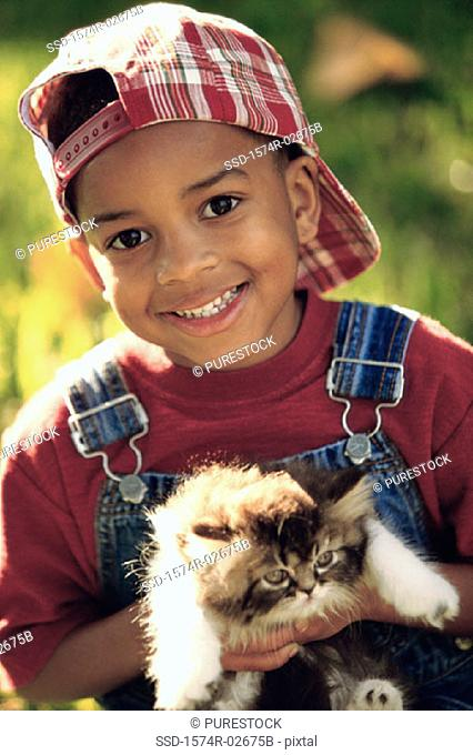 Portrait of a boy holding a cat