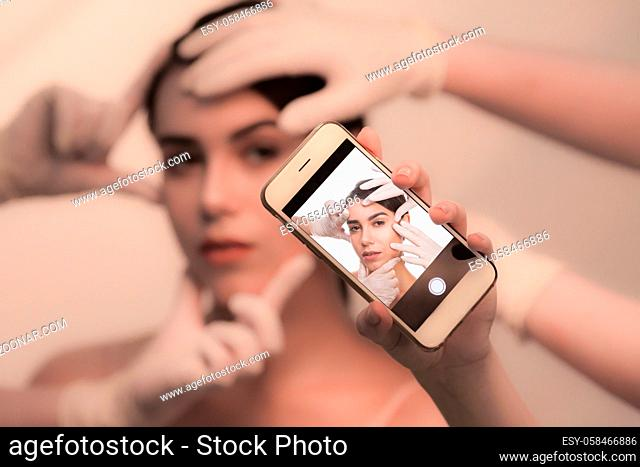 Examining face concept. Closeup pivture of mobile phone making photos of beautiful young lady while examination of her face