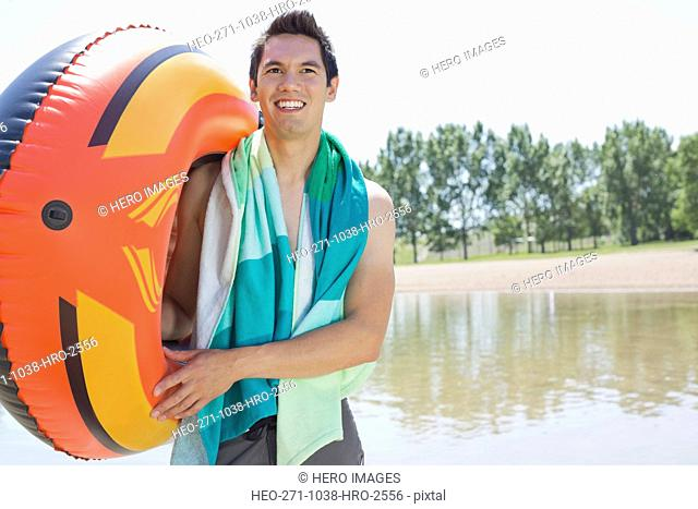Smiling man carrying inflatable raft