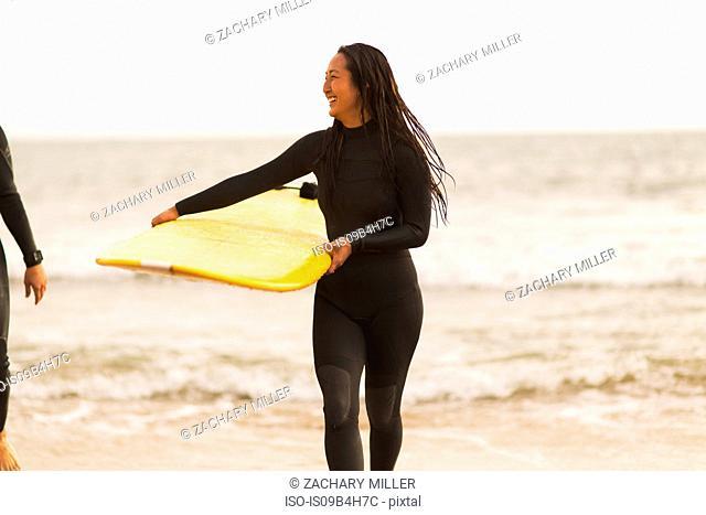 Friends walking away from sea, carrying surfboards