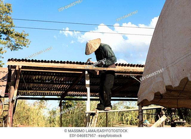 Man working on a roof in Laos