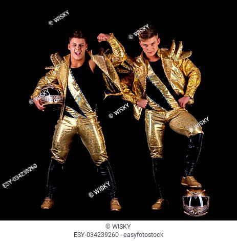 Handsome guys posing in golden dancing costumes, isolated on black