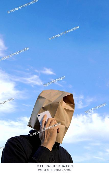 Man with paper bag above his head talking on cell phone