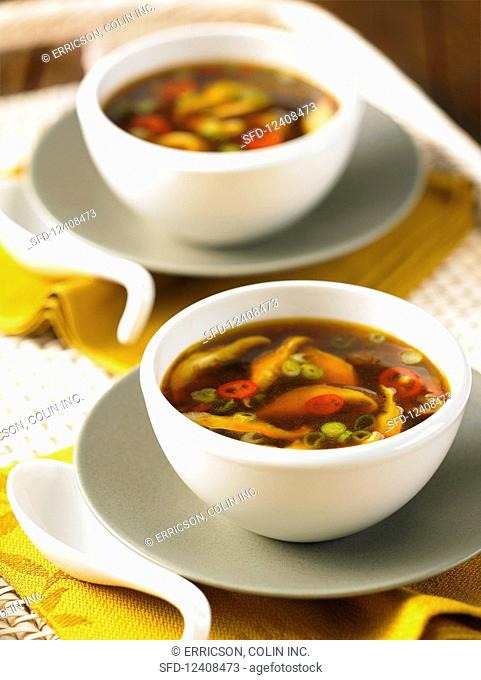 Two bowls of hot and sour Chinese soup with mushrooms
