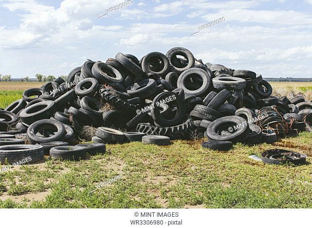 Pile of discarded auto tires, farmland in distance, near Cimarron, Kansas