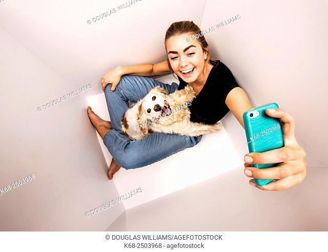 19 years old woman with cocker spaniel dog in white box taking selfie