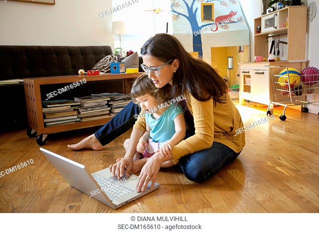 Mother and daughter sitting in front of laptop