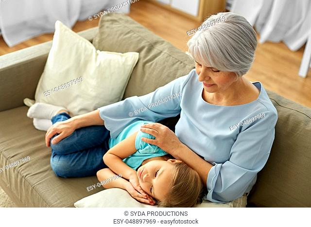 grandmother and granddaughter resting on pillow