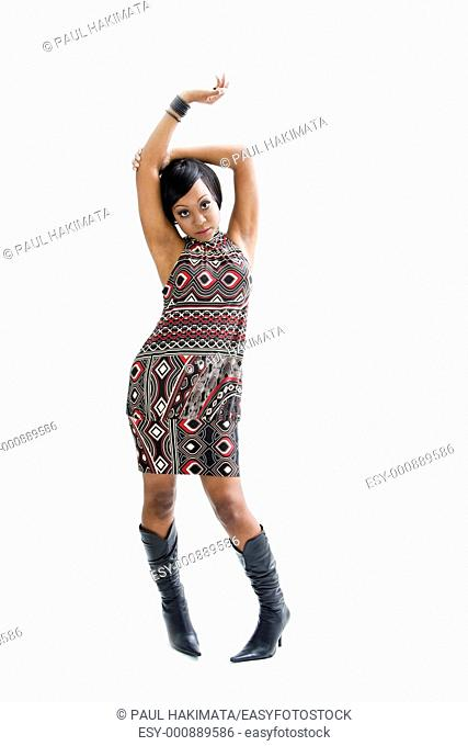 Beautiful African woman in the seventies style standing and dancing with arm up above her head, isolated