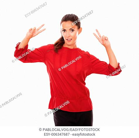 Portrait of lovely woman on red shirt with victory sign looking at you on isolated studio