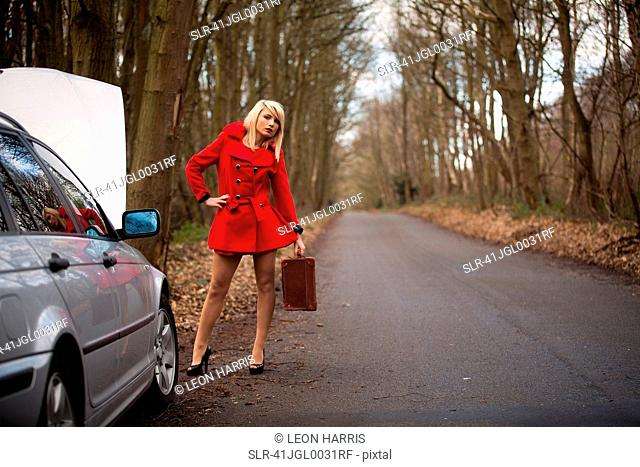 Woman with broken down car in woods