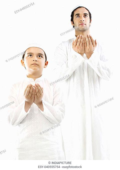 Muslim man and his son doing Namaaz
