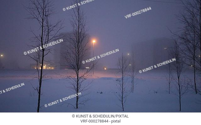 Motorway E4 on a foggy winter evening in Timra (Timrå) in northern Sweden. Cars and trucks are passing large apartment houses