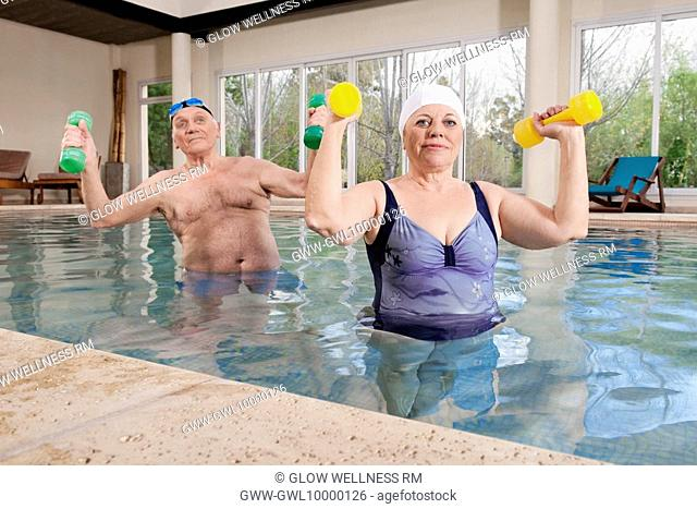 Couple exercising with dumbbells in a swimming pool