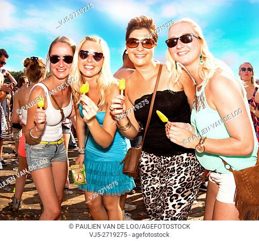 Erp, Netherlands, 4 women eating an icecream while listening to the music during an event