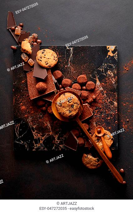 frame of homemade cookies with chocolates and candies on the marble tray and a black background