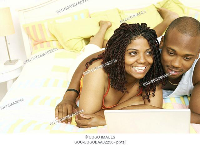 African couple using a laptop in their bedroom