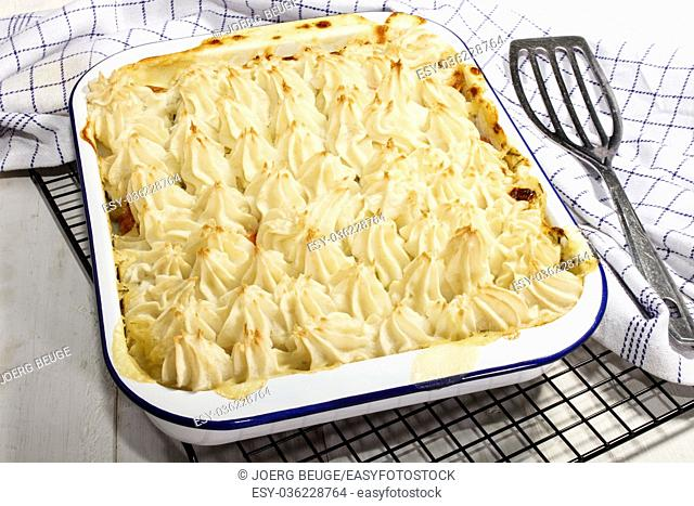 home made traditional irish fish pie in an blue and white enamel bowl