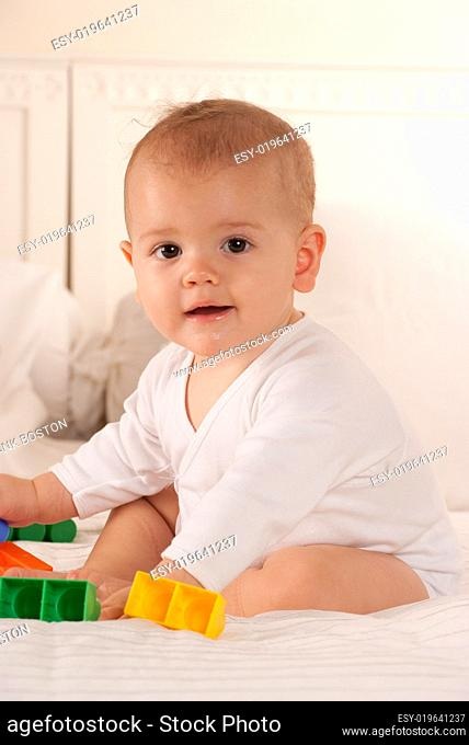 Baby playing on a bed
