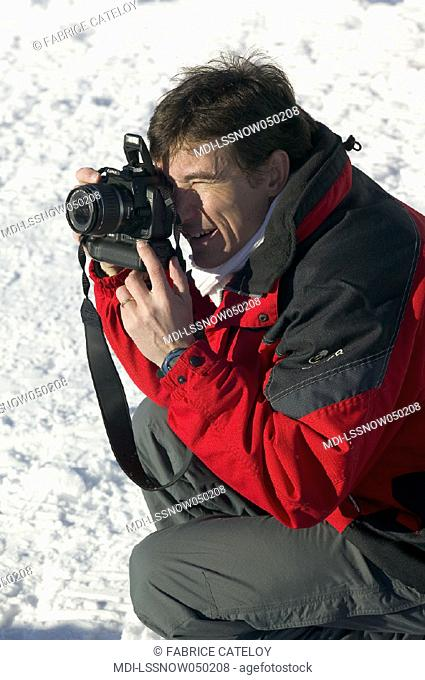 Man taking pictures in the snow