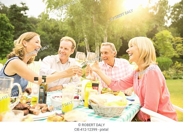 Couples toasting wine glasses at table in backyard