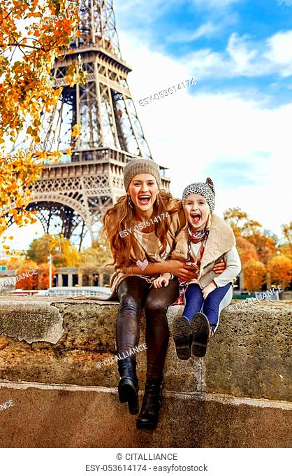 Autumn getaways in Paris with family. Portrait of smiling mother and child tourists on embankment in Paris, France having fun time