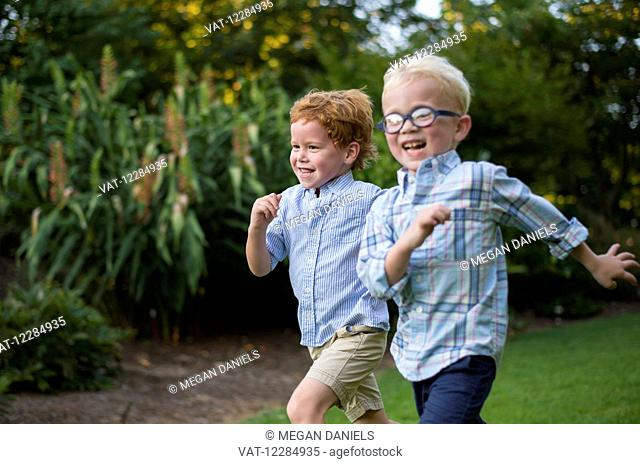 Two young boys with big smiles running together on grass; Raleigh, North Carolina, United States of America