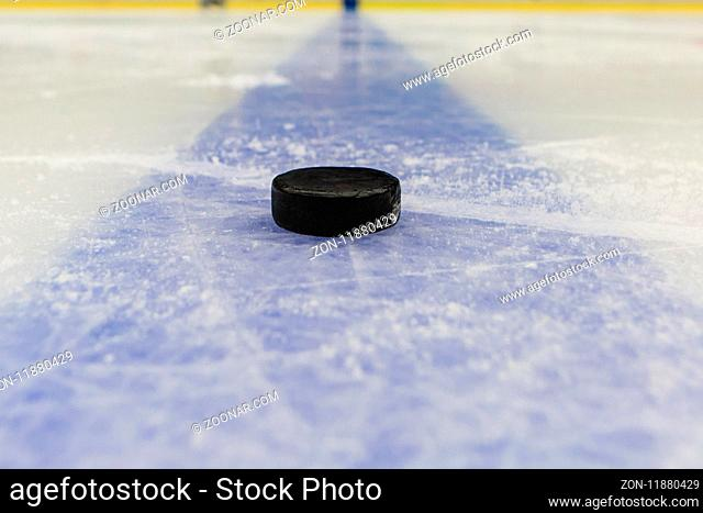 detail blue line with puck on ice hockey rink