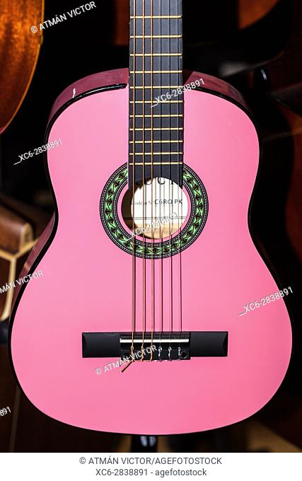 pink coloured spanish guitar for sale hanging in a music shop