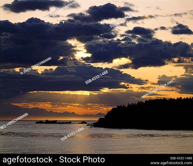 Sun setting across Shelikof Strait with view of Katmai National Park from Shuyak Island, part of the Kodiak Archhipelago, Shuyak Island State Park, Alaska