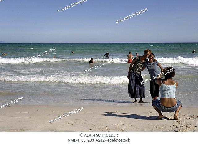 Rear view of a woman taking a photograph of two young women on the beach, Muizenberg, False Bay, Cape Town, Western Cape Province, South Africa