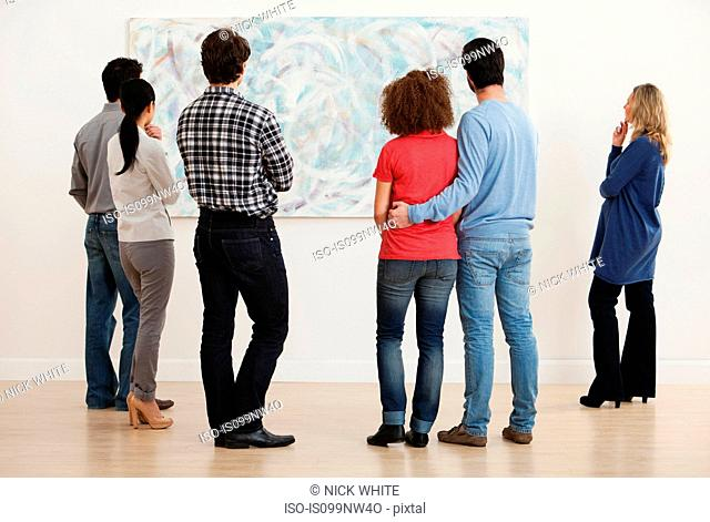 Men and women looking at oil painting in art gallery