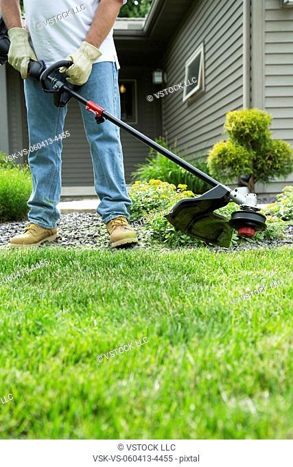 Man mowing grass in back yard