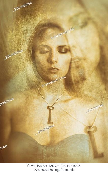 Double exposure portrait of a young woman wearing a key necklace with her eyes closed